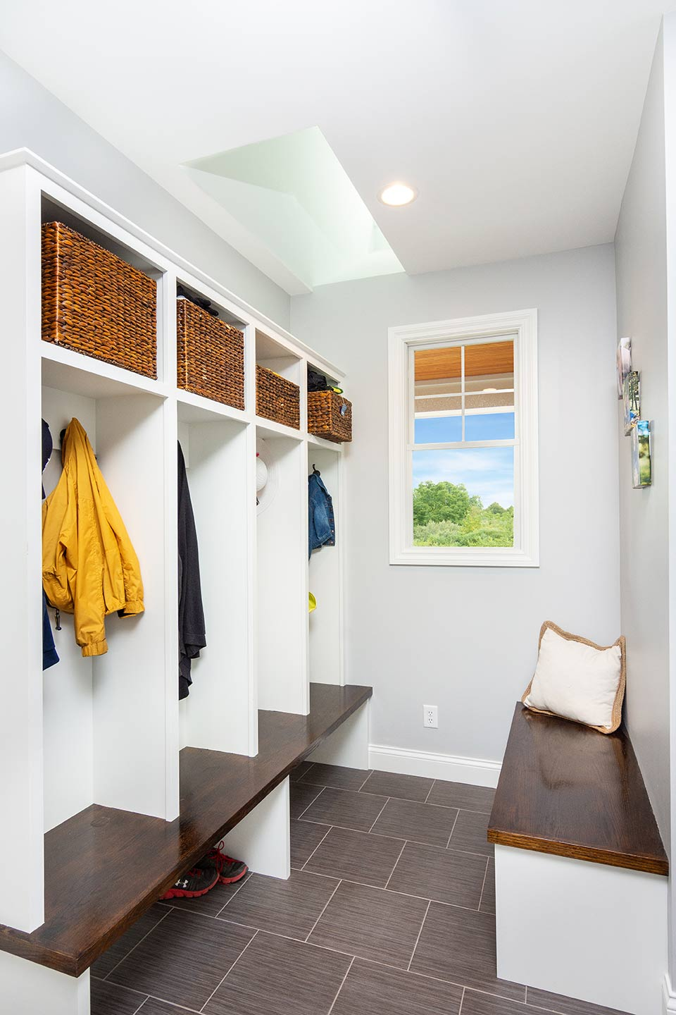 photo of mudroom with custom built-in storage shelving and a row of cubbies opposite a long bench with window and skylight