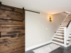 photo of remodeled basement custom built stairs and large sliding barn wood door