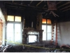 photo of severely fire-damaged living room wall with fireplace open to adjoining sun room showing large burned and broken windows on either side