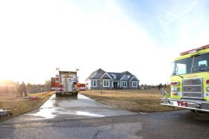 photo of fire trucks at scene of daytime house fire in Dexter, Michigan 2017 - post fire rebuilding to be undertaken by Acheson Builders