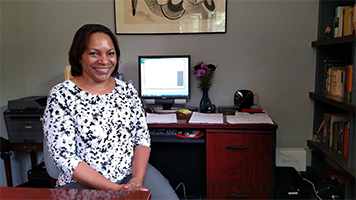 photo of Cherisse Alexander seated at desk at Acheson Builders